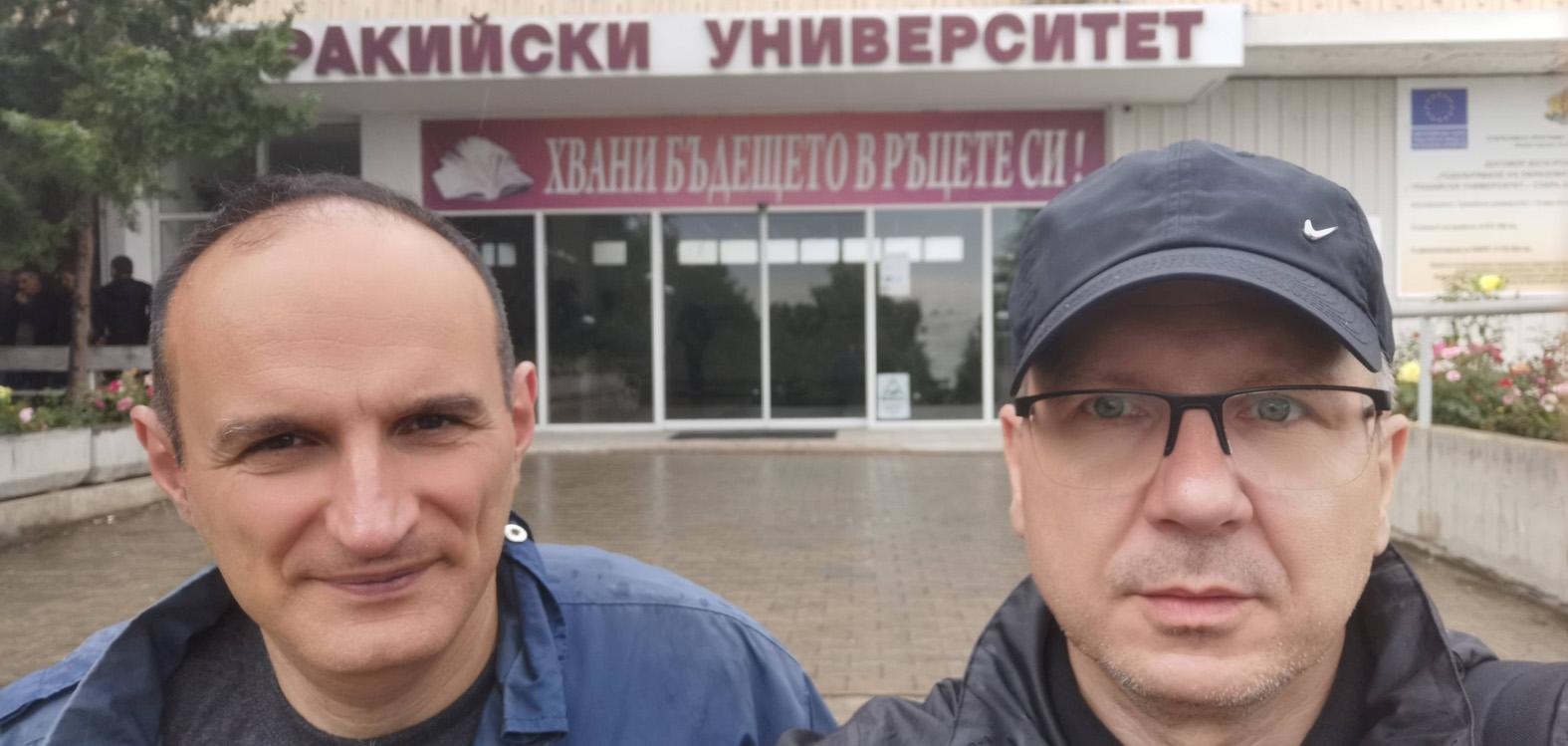 Dwóch mężczyzn stoi na pierwszym planie. W tle budynek uczelni.