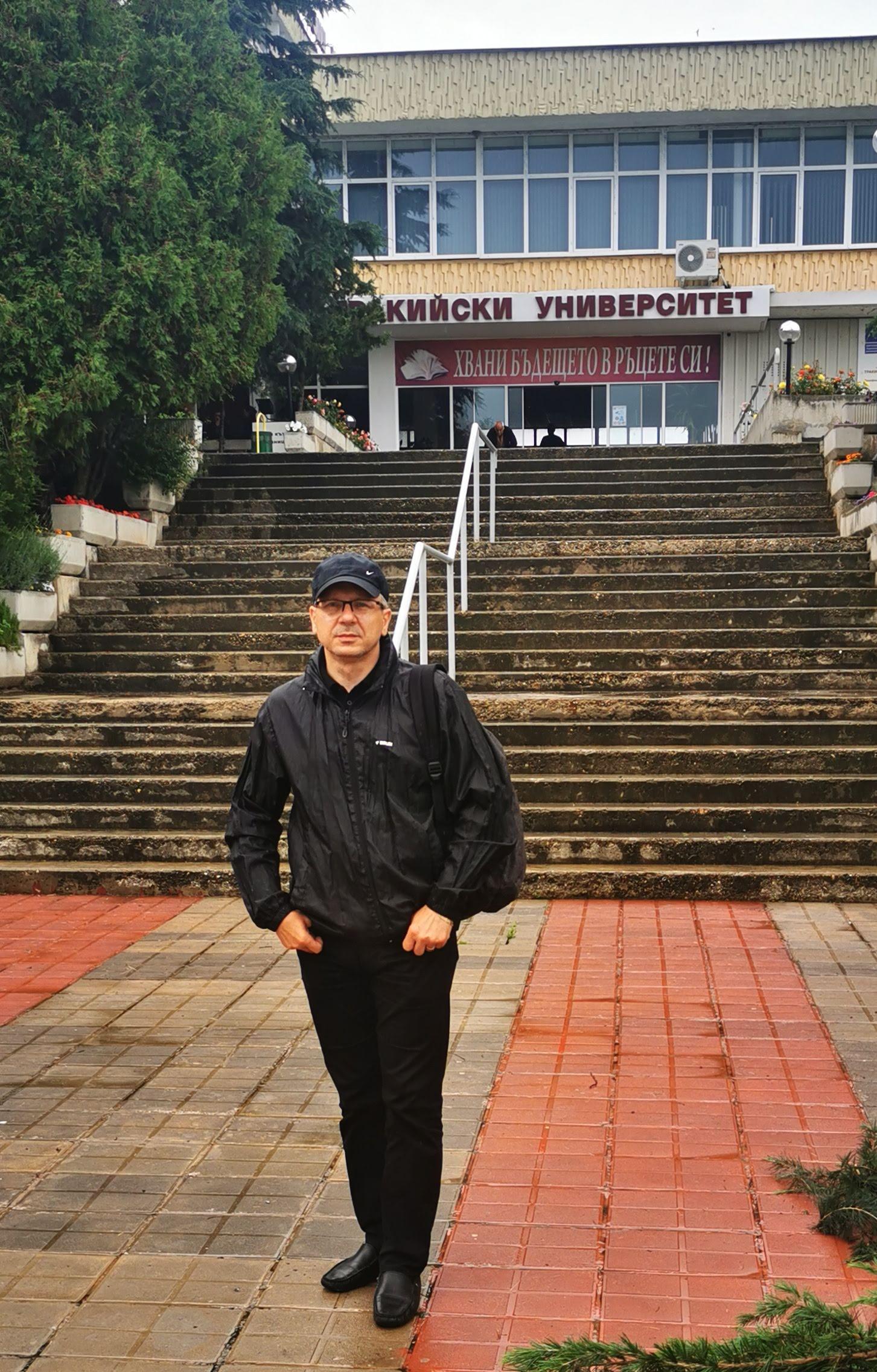 Profesor babiarz stoi na pierwszym planie. W tle schody i budynek uczelni.