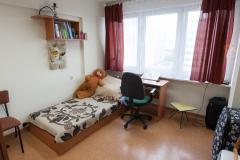 Wnętrze pokoju w akademiku. Po lewej stronie zdjęcia łóżko oraz biurko.