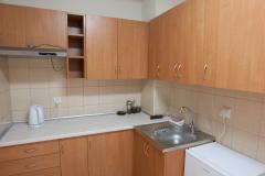 Wnętrze aneksu kuchennego. Pomieszczenie wyposażone w szafki dolne oraz wiszące, czajnik elektryczny, zlew, okap i lodówkę.