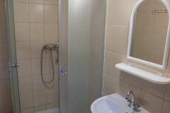 Wnętrze łazienki w akademiku. Po lewej prysznic. Po prawej umywalka, a nad nią lustro.