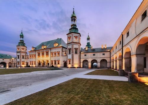 Pałac Biskupów Krakowskich w Kielcach. Zdjęcie budynku o zachodzie słońca.