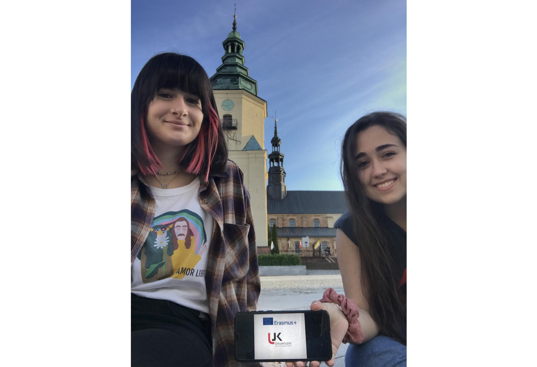 Dwie studentki siedzą. Trzymają telefon. W tle budynek Katedry.