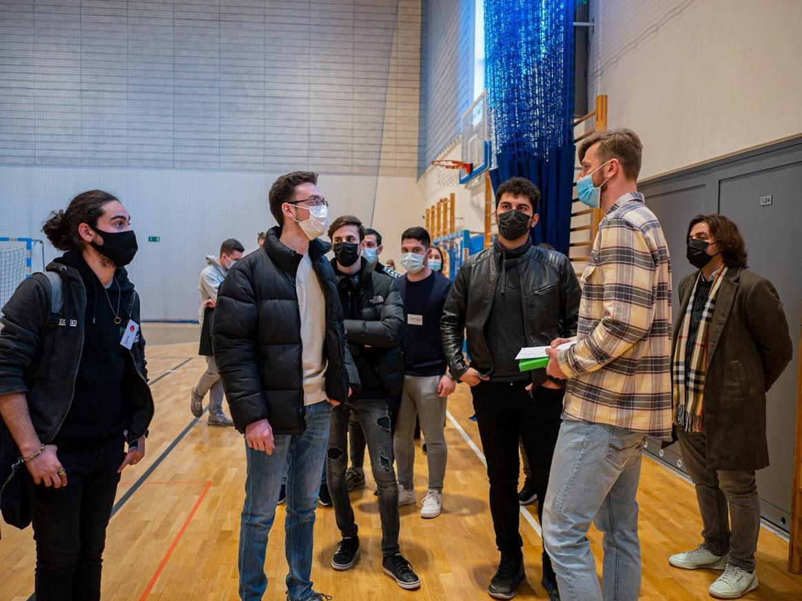 Studenci stoją i rozmawiają z wykładowcą na hali sportowej.