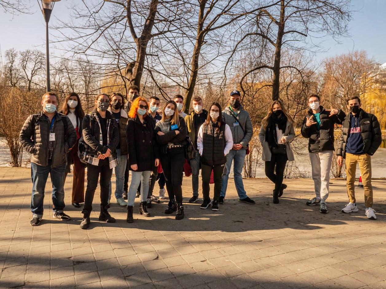 Zdjęcie grupowe. Studenci stoją w parku miejskim. W tle drzewa.
