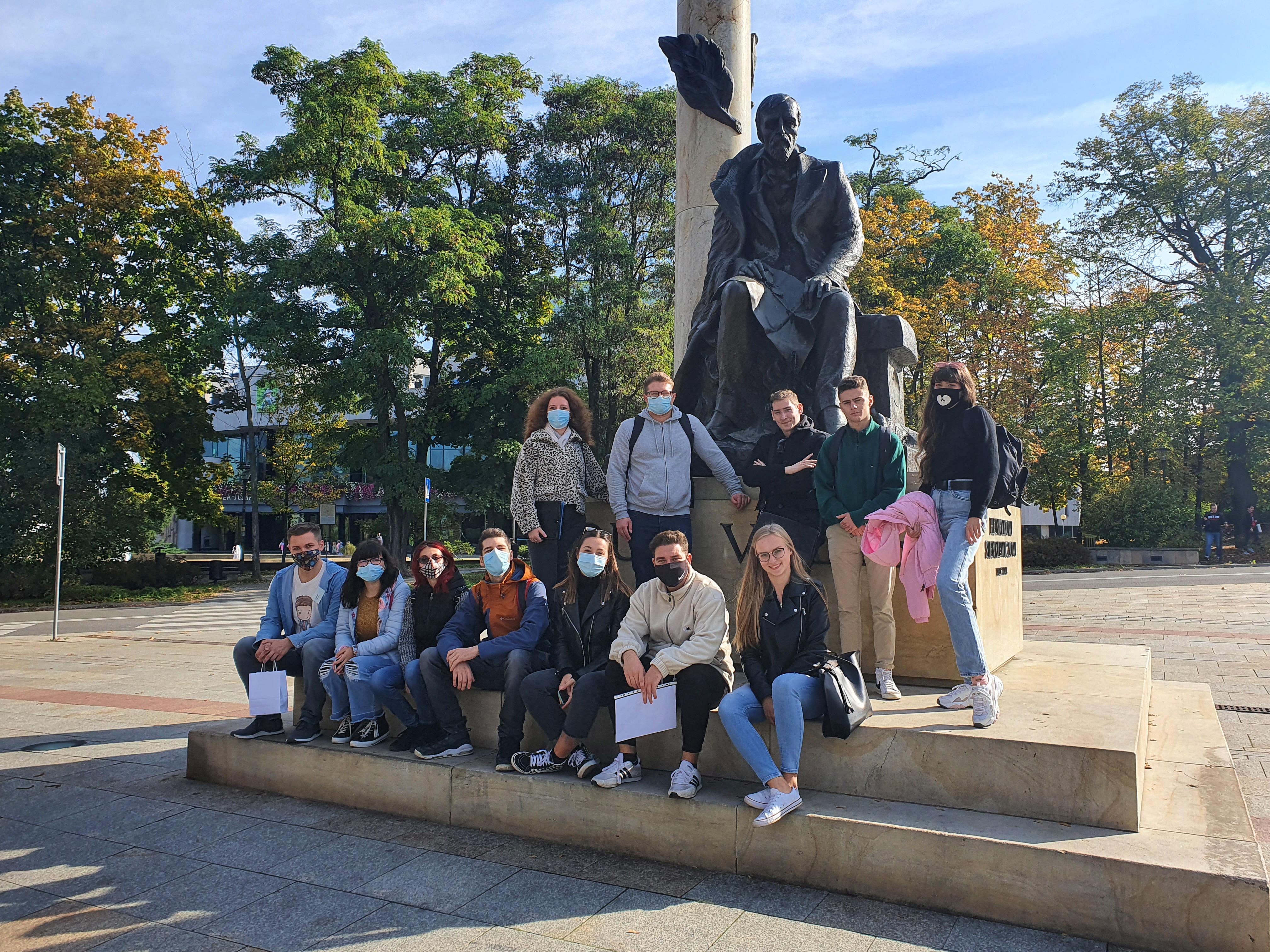 Zdjęcie grupowe studentów przy pomniku Henryka Sienkiewicza. Siedem osób siedzi. Pięć osób stoi za nimi.