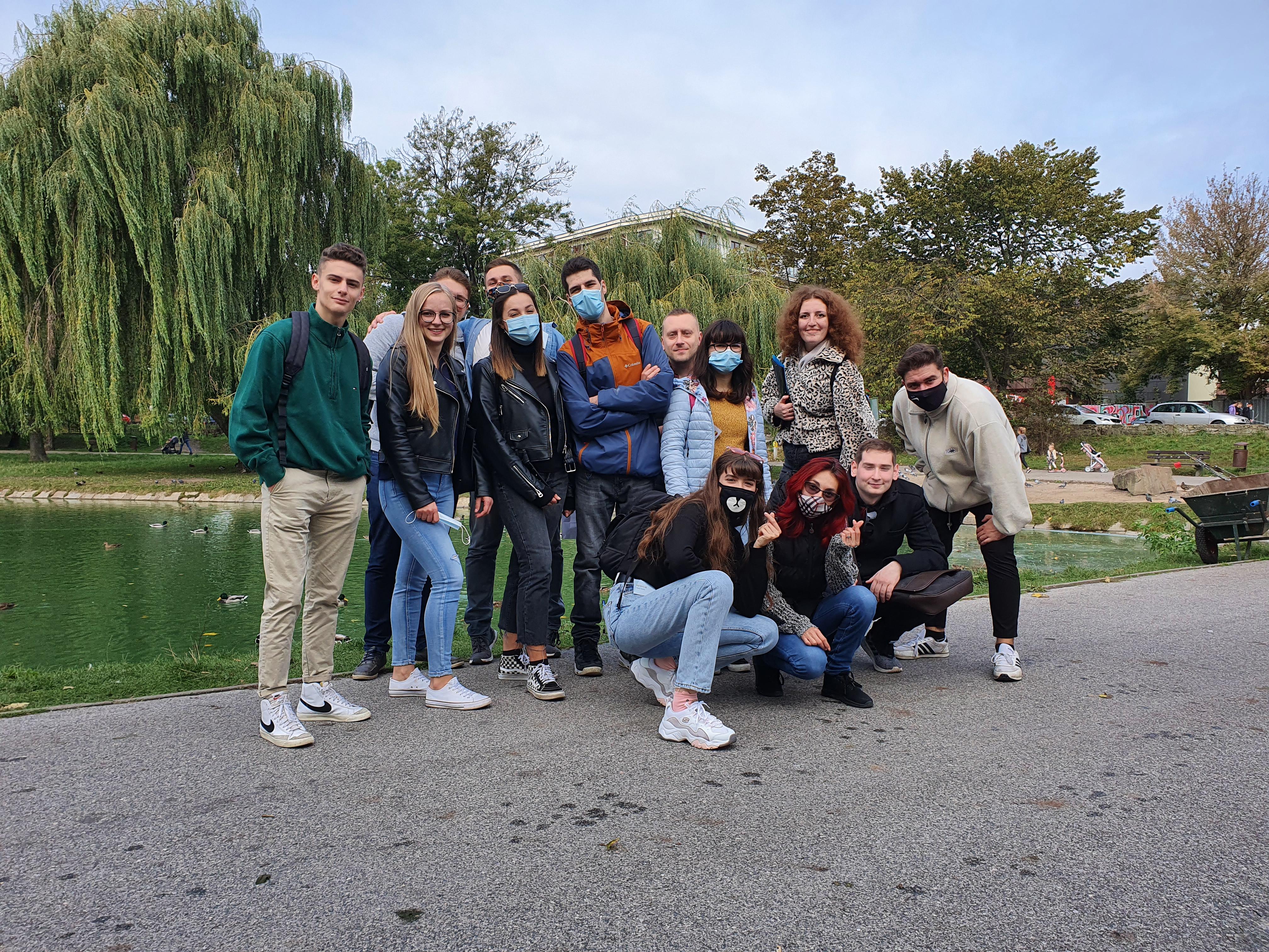 Zdjęcie grupowe studentów w parku miejskim w Kielcach. W tle drzewa i zbiornik wodny.