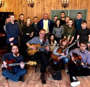 Profesor Tommy Lakso siedzi z gitarą. Otaczają go studenci oraz doktor Wojciech Lipiński. Pozostałe 3 osoby także trzymają gitary.