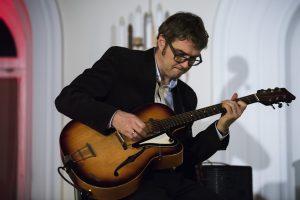 Doktor Wojciech Lipiński gra na gitarze klasycznej.
